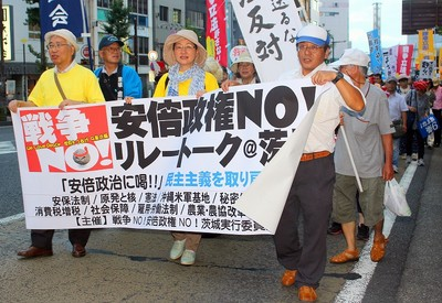 デモ行進の先頭に立つ主催者代表の田中重博氏(左)=8月23日、水戸市