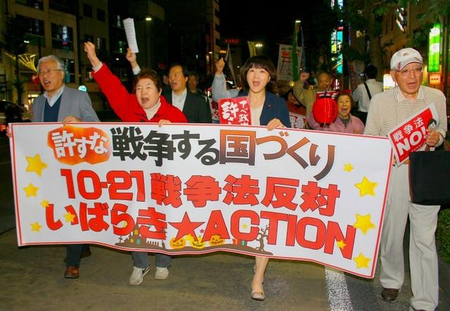 戦争法の廃止を訴えてデモ行進する梅村さえこ衆院議員(中央)と集会参加者=10月21日夕、水戸市