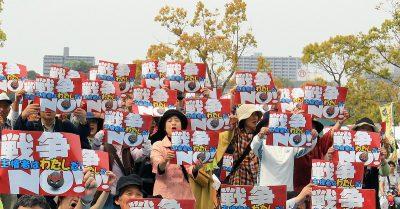 「戦争NO!」のカードをいっせいに掲げる憲法フェスティバル参加者=5月3日、水戸市