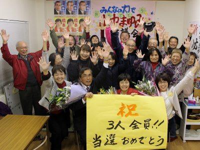 3人全員当選を喜び合う滝口氏、橋本氏、山中氏(前列左2人目から)と後援会員、支持者ら=11月14日未明、つくば市